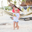 Stock Photo: Mother with her baby daughter in hammock on perfect white sand beach