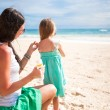 Stock Photo: Mother protects her baby from sun with suncream