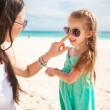 Stock Photo: Mother apply sunblock cream on her little child nose