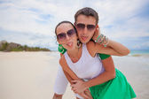 Young beautiful and happy couple showing tongue at the camera on a white beach — Stock Photo