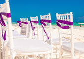 White wedding chairs decorated with purple bows on sandy beach — Stock Photo