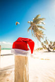 Santa Claus hat on white sandy beach in sunny day — Stock Photo