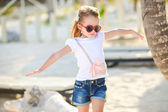 Adorable happy smiling little girl on beach vacation walks squaring arm — Stock Photo