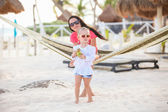 Mother with her baby daughter in hammock on a perfect white sand beach — Stock Photo