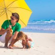 Young father and his adorable little daughter hiding from the sun under a yellow umbrella on white sunny day — Stock Photo