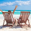 Young father with little daughter in beach chairs raised their hands up on shore ocean — Stock Photo #33459765