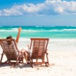 Young father with little daughter in beach chairs raised their hands up on white sand plage — Stock Photo