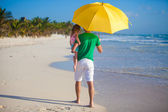 Back view of Young father and his little daughter hiding from the sun under a yellow umbrella — Stock Photo