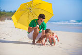 Young father and his adorable little daughter hiding from the sun under a yellow umbrella — Stockfoto