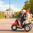 Two Little beautiful sisters sitting on toy motorcycle in autumn park — Stock Photo
