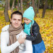 Photo: Portrait of Young father walking with his cute daughter in autumn park