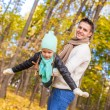 Foto Stock: Little cute girl with happy father having fun in autumn park on sunny day
