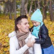 Foto Stock: Happy dad and his little girl having fun in park on sunny autumn day