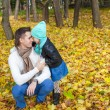 Young father and his cute little daughter whispering in autumn park — Zdjęcie stockowe #34006641