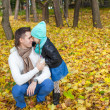 Foto Stock: Young father and his cute little daughter whispering in autumn park