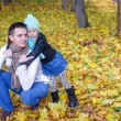 Cute little daughter with young daddy enjoy their autumn vacation on sunny day — Zdjęcie stockowe #34006843
