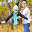 Stockfoto: Happy dad and his little daughter having fun in park on sunny autumn day
