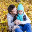 Foto Stock: Young father have fun with his cute daughter in autumn park at sunny day
