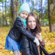 Happy mother and her cute daughter having fun in yellow autumn forest on a warm sunny day — Stock Photo #34007131