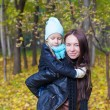Photo: Happy mother and her cute daughter having fun in yellow autumn forest on warm sunny day