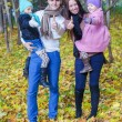 Family of four enjoying autumn vacation and showing a thumbs up — Stock Photo