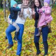 Young parents with two little daughters in autumn yellow park — Stock Photo #34007439