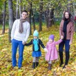 Family of four walk in autumn park on a sunny warm day — Stock Photo
