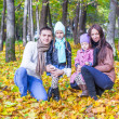 Young parents and two kids in autumn park on a sunny warm day — Stock Photo