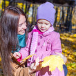 Photo: Portrait of cute girl and happy mother in yellow autumn forest on warm sunny day