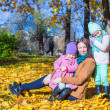Young mother with her wonderful beautiful daughters in autumn park on a sunny warm day — Stock Photo