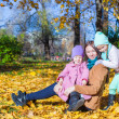 Young mother and her cute daughters in autumn park on sunny warm day — Stock Photo