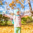 Little funny girl throws autumn leaves in park on fall day — Stock Photo