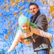 Little cute girl with happy father having fun in autumn park on a sunny day — Stock Photo