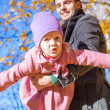 Adorable little girl with happy father having fun in autumn park on a sunny day — Stock Photo
