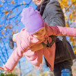 Adorable little girl with happy father having fun in autumn park on a sunny day — Stock Photo #34009151