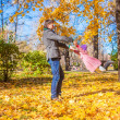 Little girl with happy father having fun in autumn park on a sunny day — Stock Photo #34009335