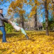 Adorable little girl with happy dad having fun in autumn park on sunny day — Zdjęcie stockowe #34009435