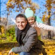 Adorable little girl with happy father having fun in autumn park on a sunny day — Foto Stock