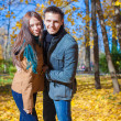 Happy family of two walking in autumn park on a sunny fall day — Stock Photo