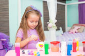 Adorable Little girl draws paints at her table in the room — Stock Photo