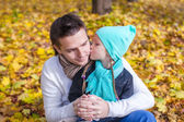 Little girl kissing happy father in autumn park outdoors — Stock Photo