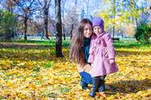 Little cute girl and young mother in autumn park on sunny day — Stock Photo