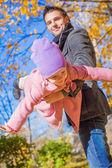 Schattig meisje met blij vader plezier in herfst park op een zonnige dag — Stockfoto