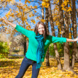 Happy young woman enjoy her autumn vacation in park — Stock Photo