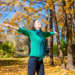 Happy young woman relaxing on autumn vacation in park — Stock Photo