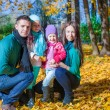 Young family with litlle girls in autumn park on sunny day — Stock Photo