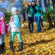 Two little girls on background of his parents at park in autumn — 图库照片 #34010529