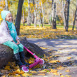 Little girl with scooter in the autumn park — Stock Photo #34011053