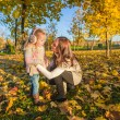 Foto Stock: Little adorable girl and young mother in autumn park on sunny day