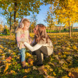 Photo: Little adorable girl and young mother in autumn park on sunny day